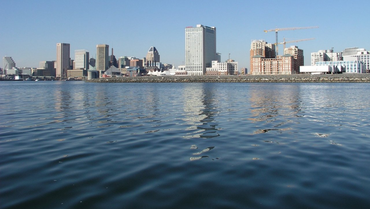 Baltimore skyline seen from the harbor, with the capped former Allied Signal site visible at the shoreline.
