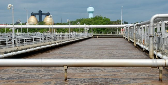 "The ""golden egg"" anaerobic digesters in the distance tower over the roiling brown water of an aeration basin at Baltimore's Back River waster water treatment plant"